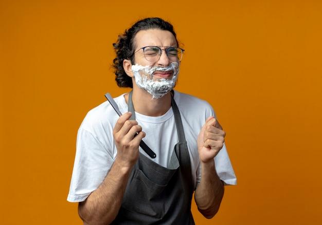 Verärgerter junger kaukasischer männlicher barbier mit brille und welligem haarband in uniform, der ein rasiermesser mit rasierschaum hält und mit geschlossenen augen auf sein gesicht legt