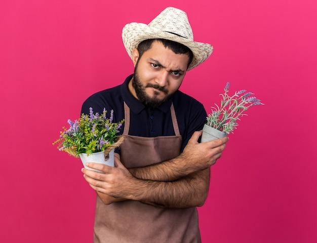 Verärgerter junger kaukasischer männlicher gärtner mit gartenhut, der blumentöpfe hält, die arme einzeln auf rosa wand mit kopienraum kreuzen