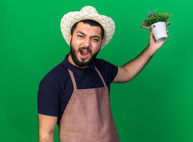 Verärgerter junger kaukasischer männlicher gärtner mit gartenhut, der blumentopf isoliert auf grüner wand mit kopienraum hält