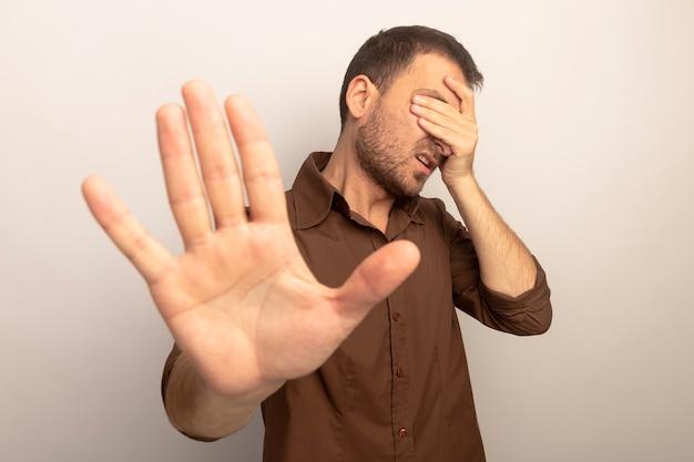Verärgerter junger kaukasischer mann, der augen mit hand bedeckt, die stoppgeste, die auf weißem hintergrund lokalisiert tut