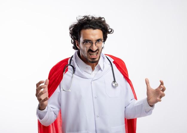 Verärgerter junger kaukasischer superheldenmann in optischer brille, der eine arztuniform mit rotem umhang und mit stethoskop um den hals trägt und in die kamera schaut