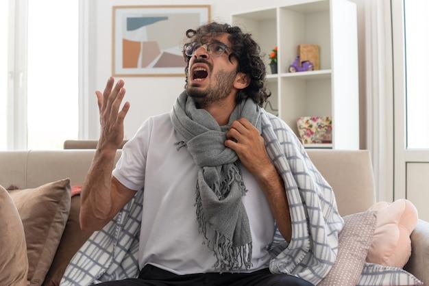 Verärgerter junger kranker kaukasischer mann in optischer brille, eingewickelt in plaid mit schal um den hals, der seitlich jemanden anschreit, der auf der couch im wohnzimmer sitzt