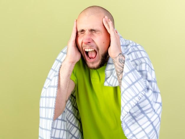Verärgerter junger kranker mann, der in plaid gewickelt ist, hält kopf mit geschlossenen augen, die auf olivgrüner wand isoliert werden