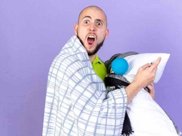 Verärgerter junger kranker mann, der in plaid gewickelt steht, steht seitlich und hält kissen mit medizinischen werkzeugen auf lila wand isoliert
