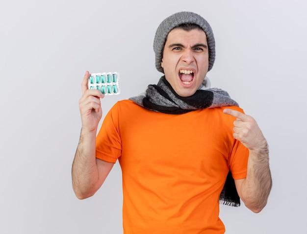 Verärgerter junger kranker mann, der wintermütze mit schal hält und punkte auf pillen isoliert auf weiß trägt