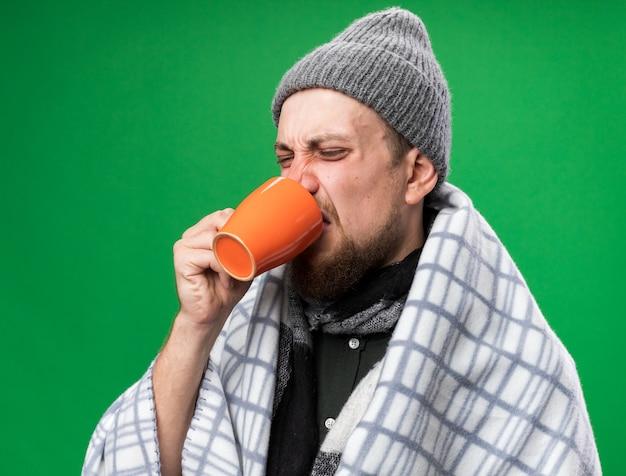 Verärgerter junger kranker slawischer mann mit schal um den hals, der in plaid gehüllt ist und winterhut trägt, trinkt aus einer tasse isoliert auf grüner wand mit kopierraum