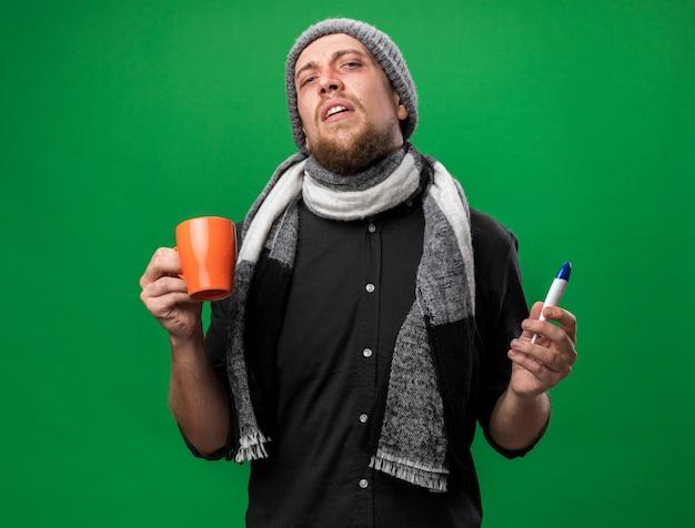Verärgerter junger kranker slawischer mann mit schal um den hals, der wintermütze mit thermometer und tasse trägt