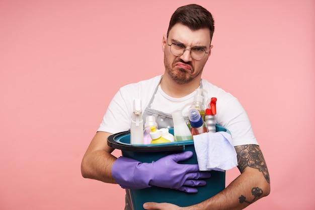 Verärgerter junger kurzhaariger brünetter mann, der eimer mit waschmitteln hält