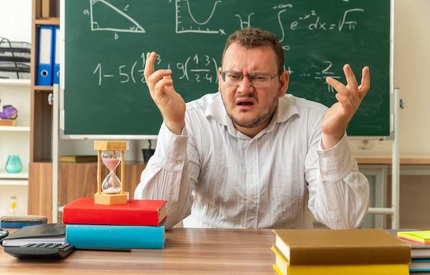 Verärgerter junger lehrer mit brille, der am schreibtisch mit schulmaterial im klassenzimmer sitzt und die hände in der luft hält und nach vorne schaut