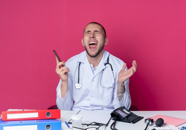 Verärgerter junger männlicher arzt, der medizinisches gewand und stethoskop trägt, sitzt am schreibtisch mit arbeitswerkzeugen, die handy halten und hand in der luft mit geschlossenen augen halten, die auf rosa lokalisiert werden