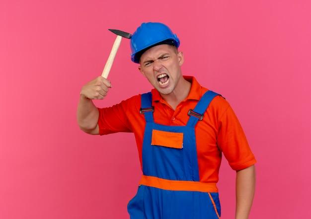 Verärgerter junger männlicher baumeister, der uniform- und schutzhelm trägt, der hammer auf helm setzt