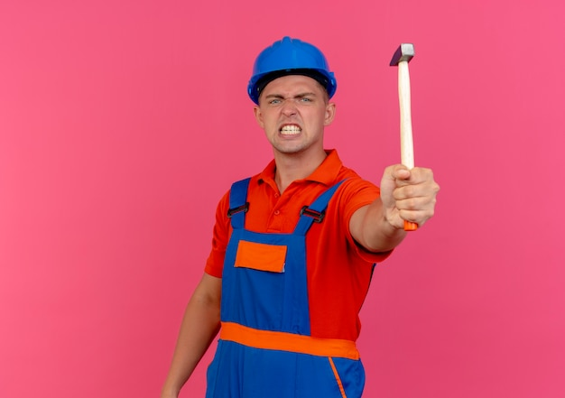 Verärgerter junger männlicher baumeister, der uniform und schutzhelm trägt, der hammer heraushält
