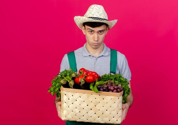 Verärgerter junger männlicher gärtner, der gartenhut trägt, hält gemüsekorb suchen