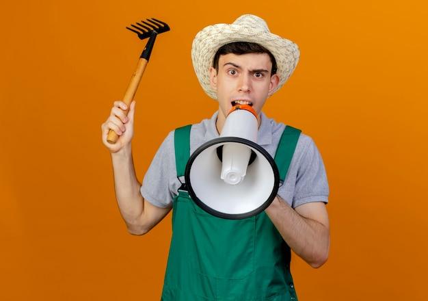 Verärgerter junger männlicher gärtner mit gartenhut hält rechen spricht in lautsprecher