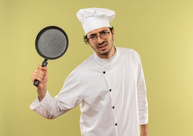 Verärgerter junger männlicher koch, der kochuniform und gläser trägt, die bratpfanne anheben