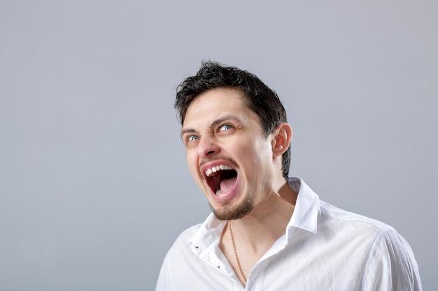 Verärgerter junger mann brunette im weißen hemd, das auf einem grauen hintergrund schreit.