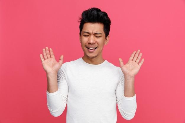 Verärgerter junger mann, der leere hände mit geschlossenen augen zeigt