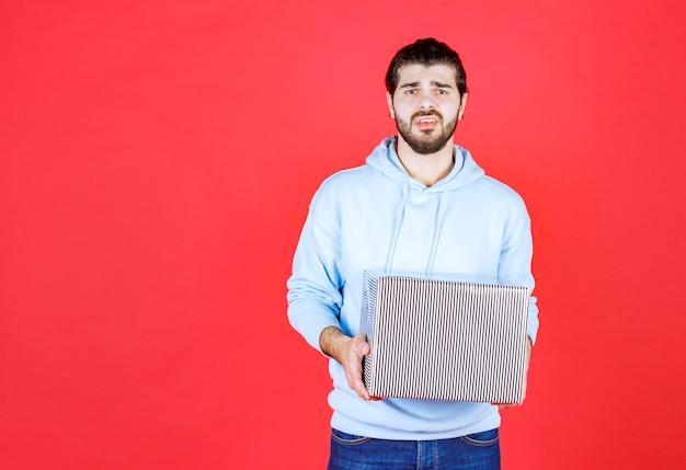 Verärgerter junger mann, der verpackte geschenkbox an roter wand hält