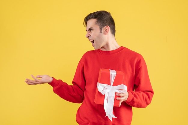 Verärgerter junger mann der vorderansicht, der auf gelb steht