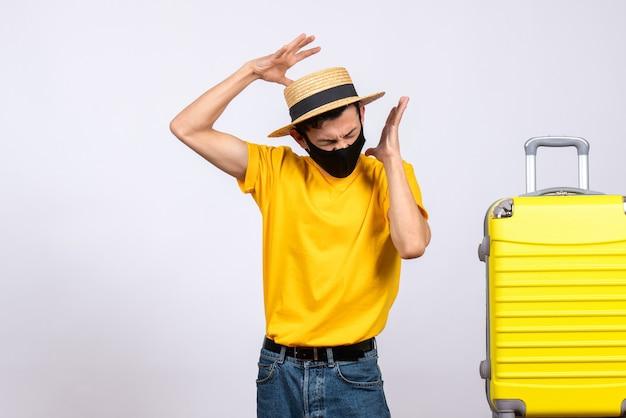 Verärgerter junger mann der vorderansicht im gelben t-shirt, der nahe gelbem koffer steht