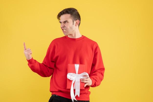 Verärgerter junger mann der vorderansicht mit dem roten pullover, der auf gelb steht