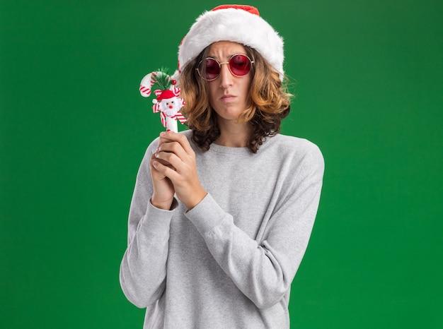 Verärgerter junger mann, der weihnachtsweihnachtsmütze und rote brille hält, die weihnachtszuckerstange hält, die kamera mit traurigem ausdruck betrachtet, der über grünem hintergrund steht