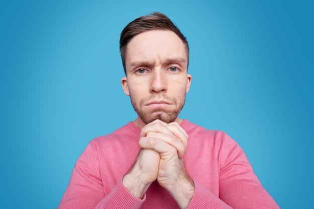 Verärgerter junger mann im rosa pullover, der seine hände am kinn hält, während er überlegt, was zu tun ist