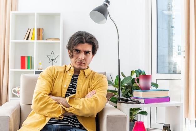 Verärgerter junger mann in freizeitkleidung, der mit ernstem gesicht mit verschränkten armen auf dem stuhl im hellen wohnzimmer sitzt