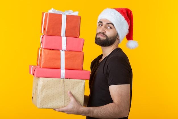 Verärgerter junger mann mit bart in einer weihnachtsmannmütze hält fünf geschenkboxen, die auf einem gelben posieren