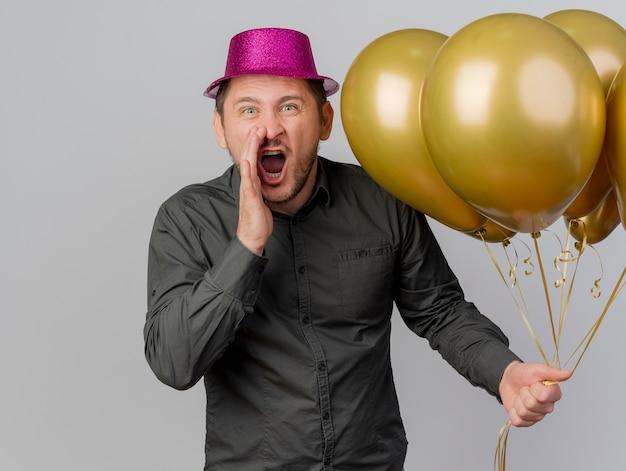 Verärgerter junger party-typ, der rosa hut trägt, der luftballons hält und jemanden lokalisiert auf weiß ruft