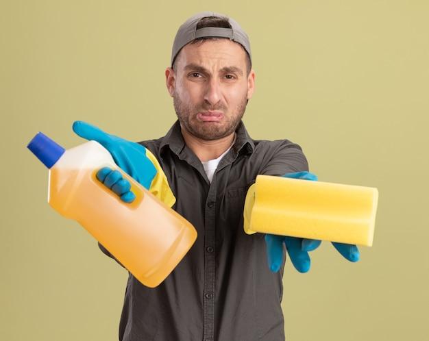 Verärgerter junger reinigungsmann, der freizeitkleidung und kappe in den gummihandschuhen hält, die flasche mit reinigungsmitteln und schwamm halten, die weinen, die spitzen lippen stehen über grüner wand stehen