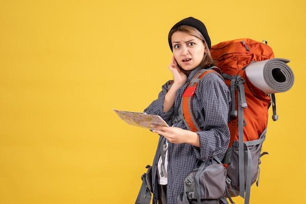 Verärgerter junger reisender mit rucksack mit karte