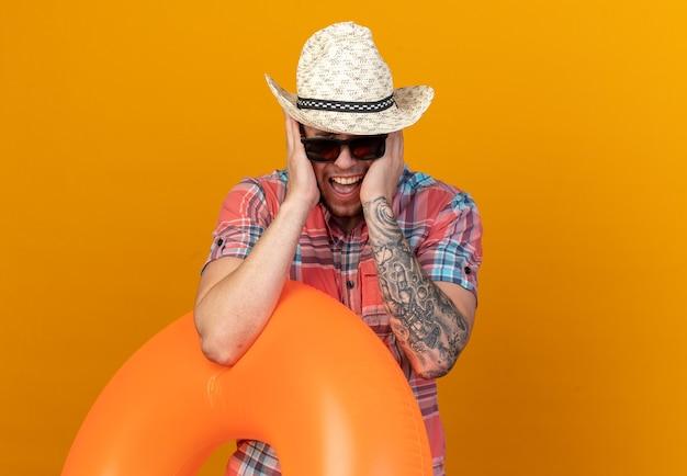 Verärgerter junger reisender mit strohhut in sonnenbrille, der schwimmring hält und seine ohren mit den händen schließt, die auf orangefarbener wand mit kopienraum isoliert sind