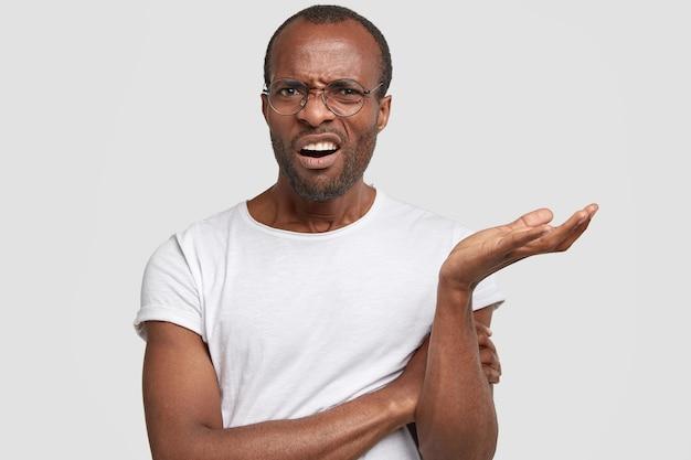 Verärgerter junger schwarzer mann runzelt die stirn, zuckt mit den schultern und fühlt sich ahnungslos