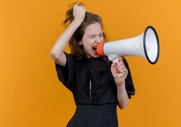 Verärgerter junger slawischer weiblicher friseur, der uniform trägt, die im lautsprecher schreit und haare mit geschlossenen augen zieht, lokalisiert auf orange hintergrund mit kopienraum