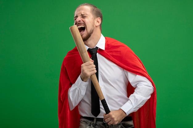 Verärgerter junger superheld, der krawatte mit geschlossenen augen trägt, die baseballschläger lokalisiert auf grün halten