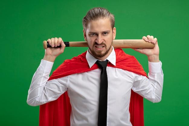 Verärgerter junger superheld, der krawatte trägt, die baseballschläger hinter hals isoliert auf grün isoliert
