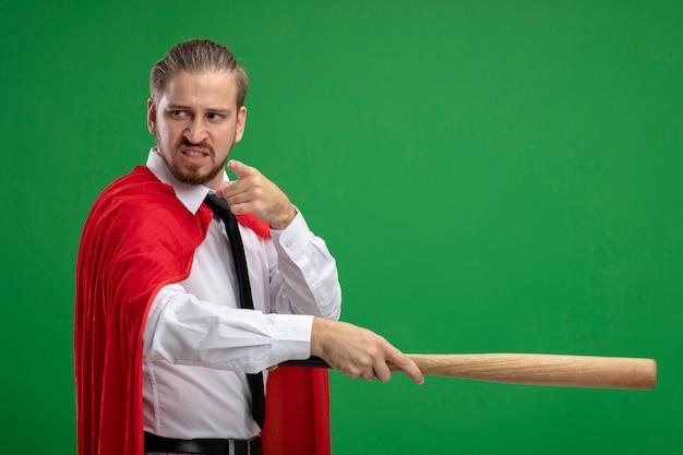 Verärgerter junger superheld, der krawatte trägt, die sie geste zeigt und baseballschläger an der seite lokalisiert auf grünem hintergrund hält