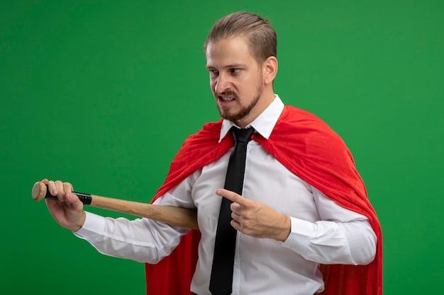 Verärgerter junger superheld, der krawattenhaltung trägt und auf baseballschläger zeigt, der auf grün lokalisiert wird
