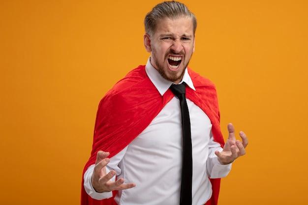 Verärgerter junger superheld kerl, der kamera trägt krawatte lokalisiert auf orange hintergrund betrachtet