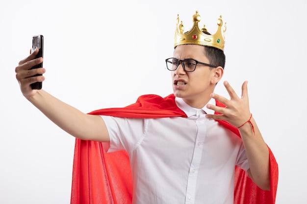 Verärgerter junger superheldenjunge im roten umhang, der brille und krone trägt hand in der luft hält selfie lokalisiert auf weißem hintergrund