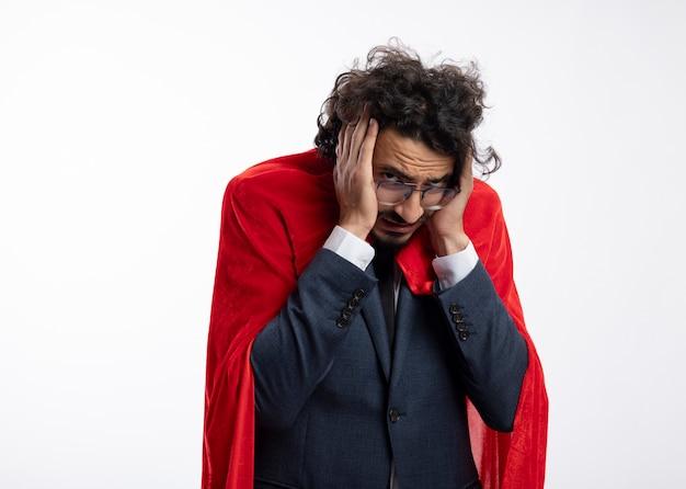 Verärgerter junger superheldenmann in der optischen brille, die anzug mit rotem umhang trägt, hält kopf lokalisiert auf weißer wand