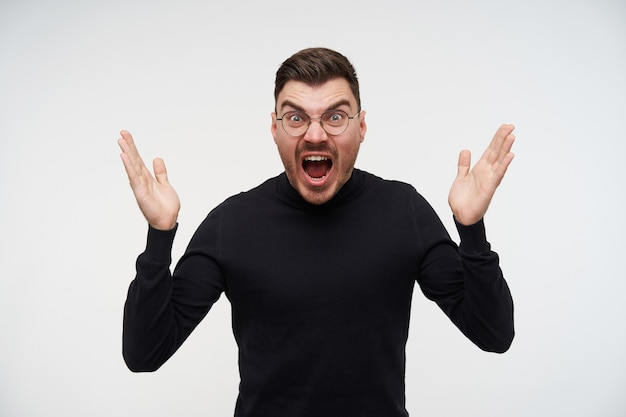 Verärgerter junger, ziemlich kurzhaariger, brünetter mann mit brille, der sein gesicht runzelte, während er verärgert schrie und emotional die hände hob, isoliert auf weiß