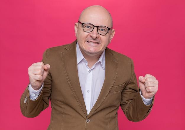 Verärgerter kahler mann mittleren alters im anzug, der eine brille mit aggressivem ausdruck trägt, die über der rosa wand steht