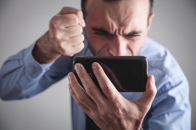Verärgerter kaukasischer geschäftsmann mit smartphone.
