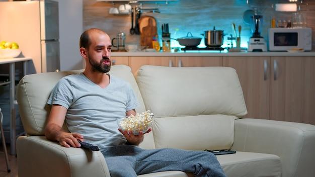 Verärgerter kaukasischer mann, der allein ein sportmatch anschaut