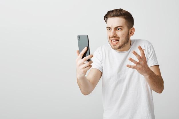 Verärgerter kerl, der videoanruf spricht, schimpft und jemanden über video-chat mit handy anschreit