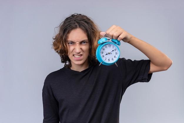 Verärgerter kerl mit langen haaren im schwarzen t-shirt, der einen wecker auf weißer wand hält