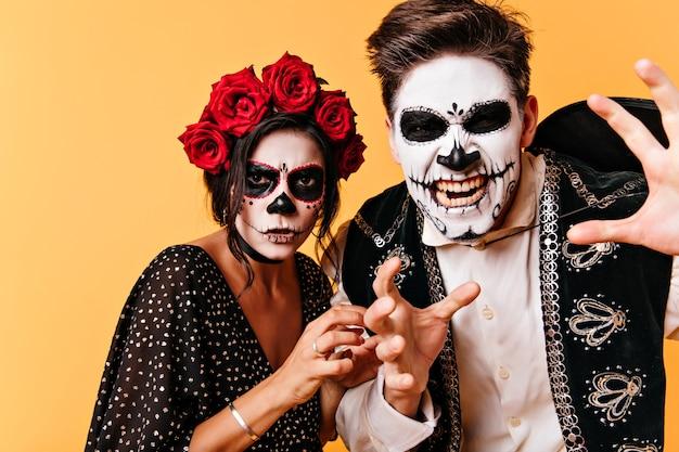 Verärgerter kerl mit mexikanischer gruseliger maske, die aufwirft. stilvolles zombie-paar, das in halloween herumalbert.