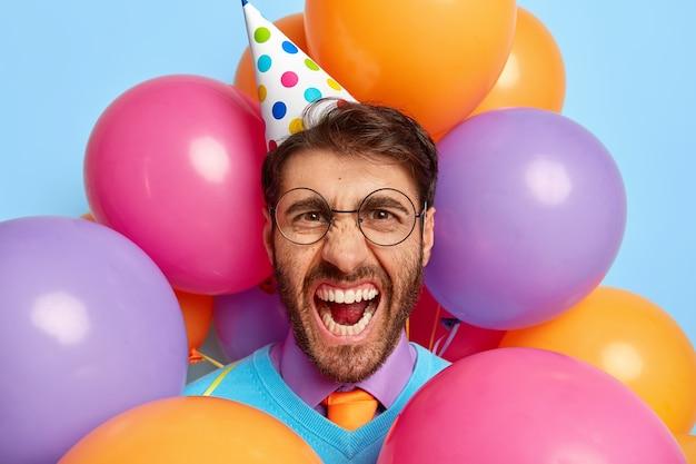 Verärgerter kerl umgeben von partyballons posierend